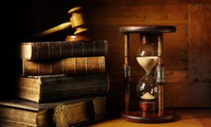 Image of sand timer and stack of books, with a judge's hammer on top of the books